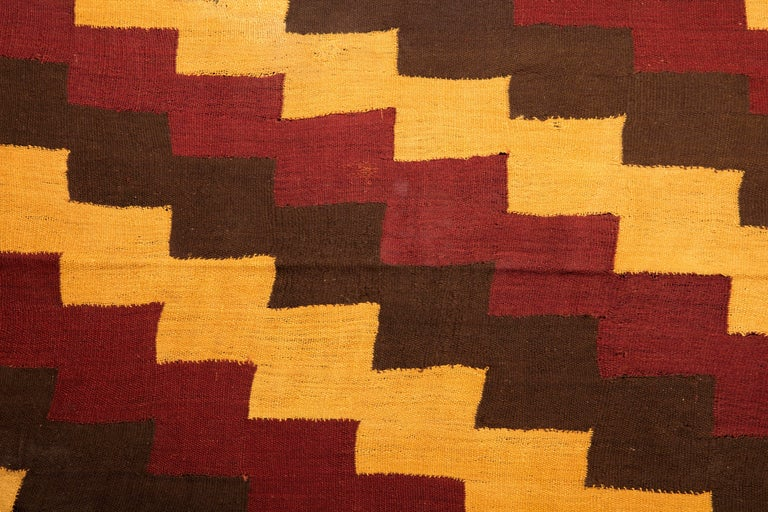 Complete Pre-Columbian Nazca textile with stepped zig-zag design in yellow, ochre red, and brown/black shades with yellow fringes.