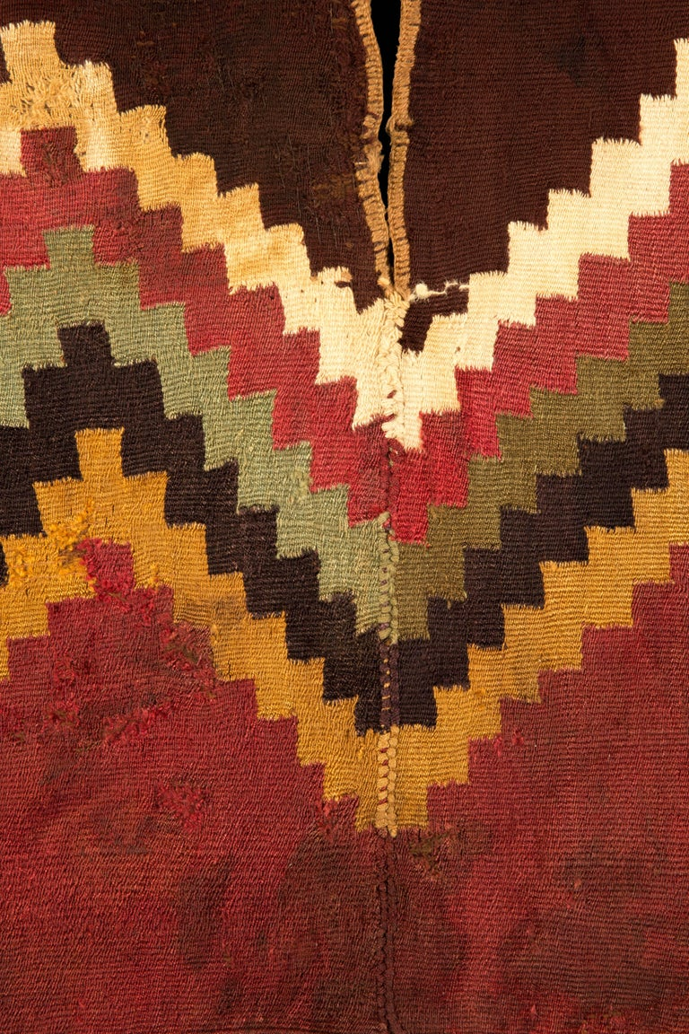 Complete Nazca unku with white, red, green, black and yellow step zig-zag design with red bottom with fringe and maroon upper part and beige trim around the arm and neck openings  200-300 CE  Nazca, Peru  Size: 38 in x 18 in.