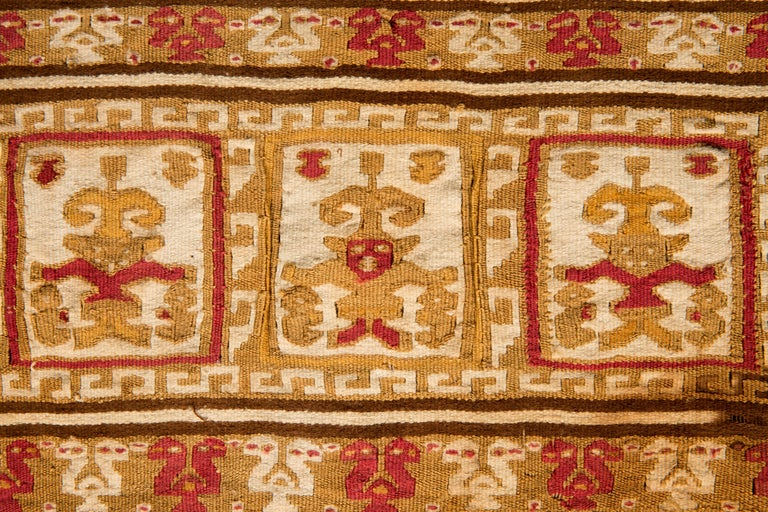 Pre-Columbian ornamental banner with fringes composed of warriors/divinities holding figures in their hands, surrounded by geometric frets. Two-headed birds in alternating colors decorate the top and bottom of the banner. This one-of-a-kind tapestry