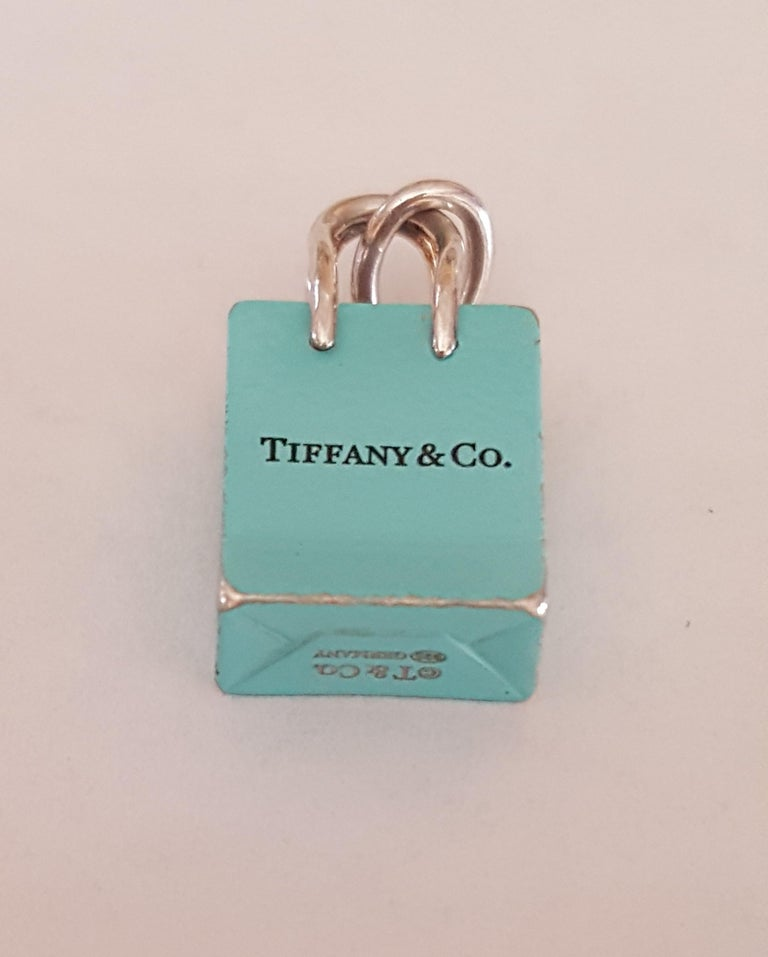 Pre-owned Tiffany & Co. Silver Signature Blue Purse Pendant , Enamel finish, Hallmark: T and Co. Germany, 11mm x 13 mm x 5.5mm in size. Good condition, the enamel has worn slightly on the bottom of pendant. Iconic piece for a Tiffany Co Collector.