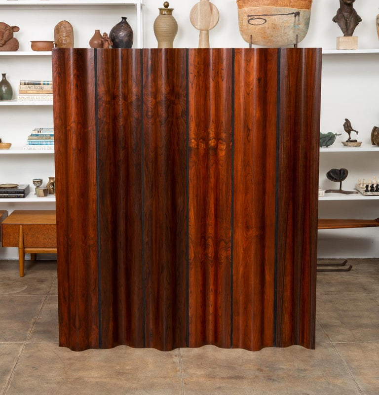 Ray and Charles Eames iconic folding screen for Herman Miller, in rosewood. When the harvesting of Brazilian rosewood became illegal in 1992, Herman Miller ceased purchasing it for their Eames lounge chairs. They took their remaining rosewood stock