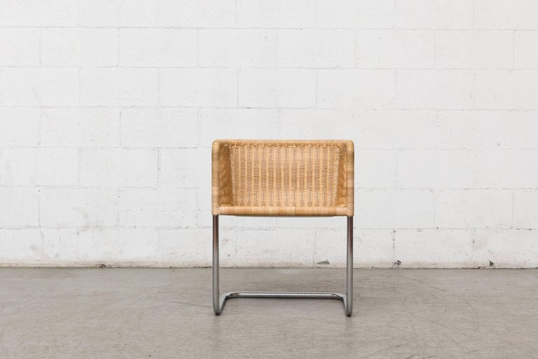 Cantilevered woven rattan chair designed by Preben Fabricius & Jorgen Kastholm. Wicker bucket seat on a cantilevered chrome frame. Original condition.