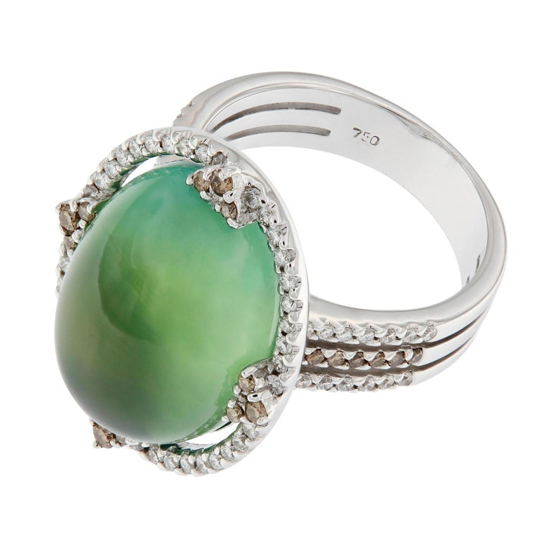 This 18k white gold ring centers around a cabochon cut Prehnite. An intriguing gemstone that features a unique green glow and is known as the stone of prophecy, aiding in spiritual communication through meditation. Center stone is accented with