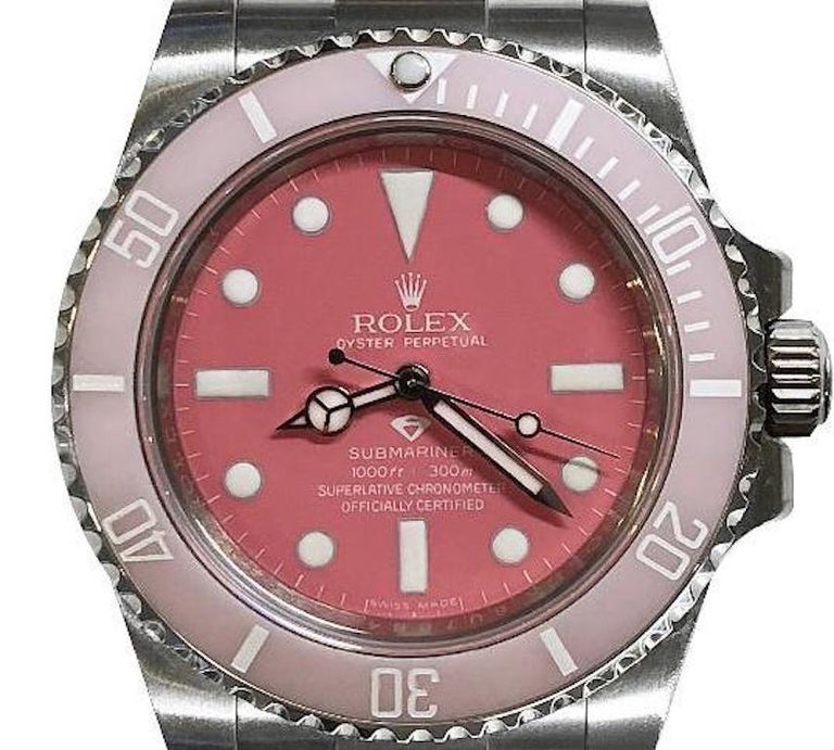 Manufacturer: Rolex  Model number: 114060  Model: Submariner   Model Case: Oyster  Diameter: 40 mm  Material: Oyster steel  Bezel: Unidirectional rotatable 60-minute graduated, customized in light pink with a baby pink dial  Glass: Scratch-resistant