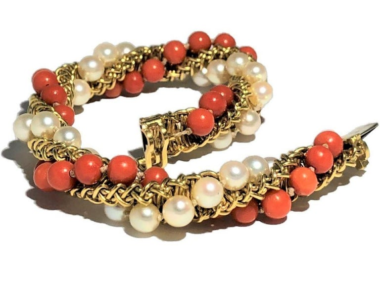 This very interesting 18k yellow gold French Cartier designed and created orange coral and Japanese cultured pearl cocktail bracelet is both casual and elegant. It is substantial in appearance with a diameter of almost 1/2 inch and a length of 7 3/8