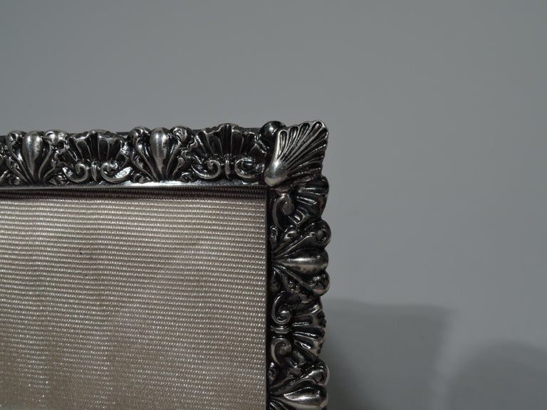 Pretty sterling silver picture frame. Made by Bigelow, Kennard & Co. in Boston, ca 1900. Rectangular window surrounded by alternating tooled shells and leaves. With glass, silk lining, and hinged silver wire support. Fully marked. 