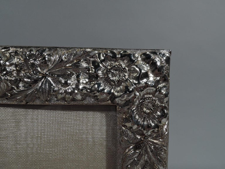 Beautifully ornate sterling silver picture frame. Made by Stieff in Baltimore in 1925. Rectangular window and repousse floral surround with abundant blooms. Interlaced script monogram engraved on rail top. A great piece by a premier regional maker.