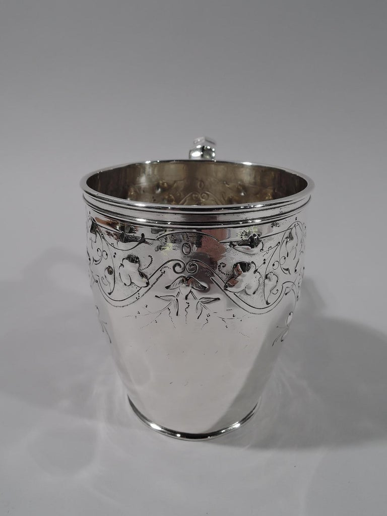 Pretty coin silver baby cup. Gently curved and tapering body and capped scroll-bracket handle. Stylized ornament with loose and scattered flowers in pendant strapwork frames. Numbered 50 with maker's stamp for Krider & Biddle, a partnership that was