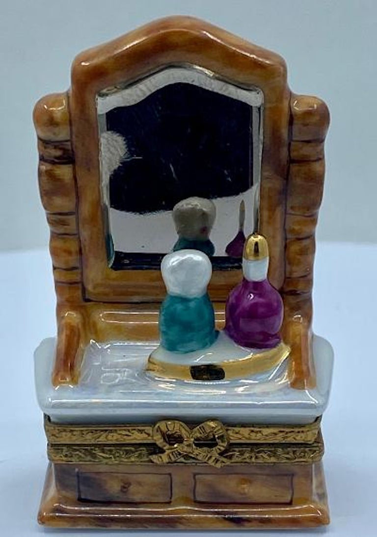 Collectible and very unique, Limoges porcelain miniature trinket box is handmade and hand painted in France and features a very detailed vanity or dresser with attached mirror and a tray on top with perfume bottles. Beautiful wood grain finish,