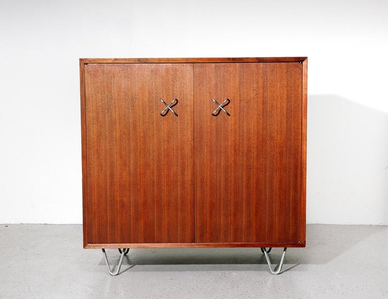 Primavera cabinet designed by George Nelson for Herman Miller. Mahogany cabinetry with zinc-plated X-pulls and hairpin legs.