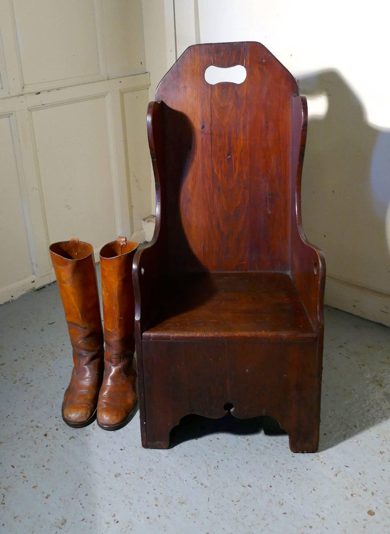Primitive 19th century American pine Childs Country chair  This a rare piece, made in America a primitive 19th century upright child's chair, the chair has shaped sides and arched back with a pierced hand hold. The chair is made in age darkened
