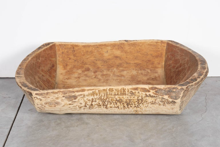 An antique Chinese bowl carved from a single piece of pine wood. This piece has a striking, irregular shape and shows the beautiful wear which is the result of more than one hundred years of use. 