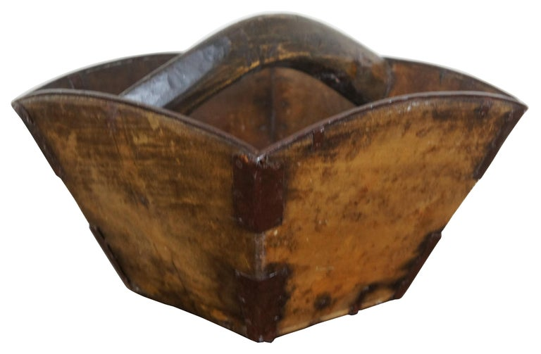 Antique Asian wooden rice bucket with metal reinforced corners, tapered square shape and handle across the middle. Measures: 13