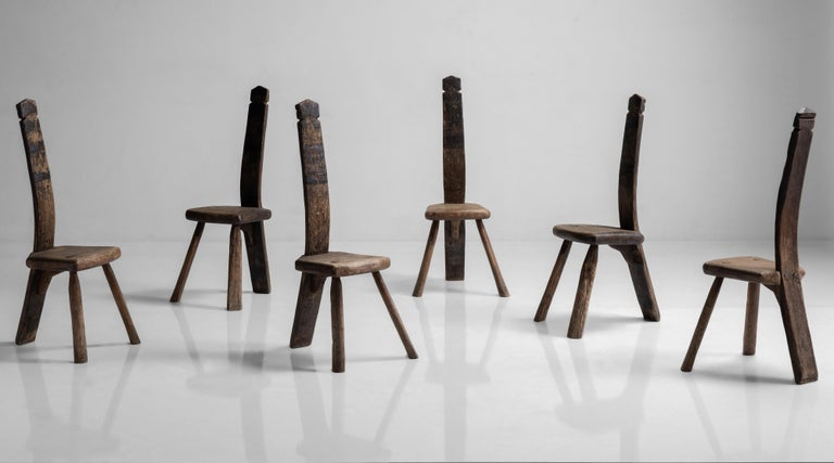 Constructed in oak. Unique form, slab seat with peg legs and curved carved wooden back.   Measures: 14