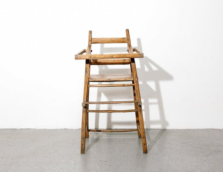 Early American child's high-chair. Features a swing down table and footrest. Spartan construction and features.  Size: 19