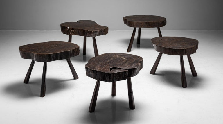 Slab top tables on three splayed legs. Original dark finish.