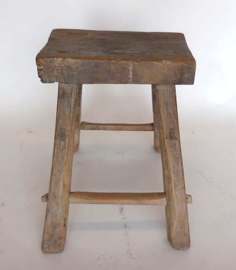 Antique Chinese Primitive elm wood stool with flared legs. Mortise and tenon construction. Great old weathered patina. The seat measures 17.25 by 11 by 3 inches thick.