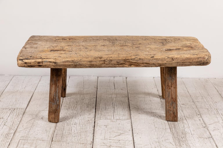 Primitive French wooden table with four splayed legs. The wood is old and offers unique grain.