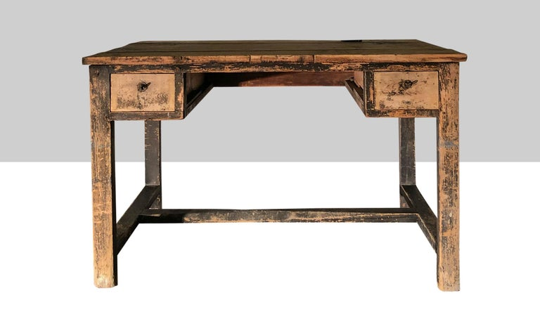 Two-drawer desk in worn period finish with remnants of the original paint.