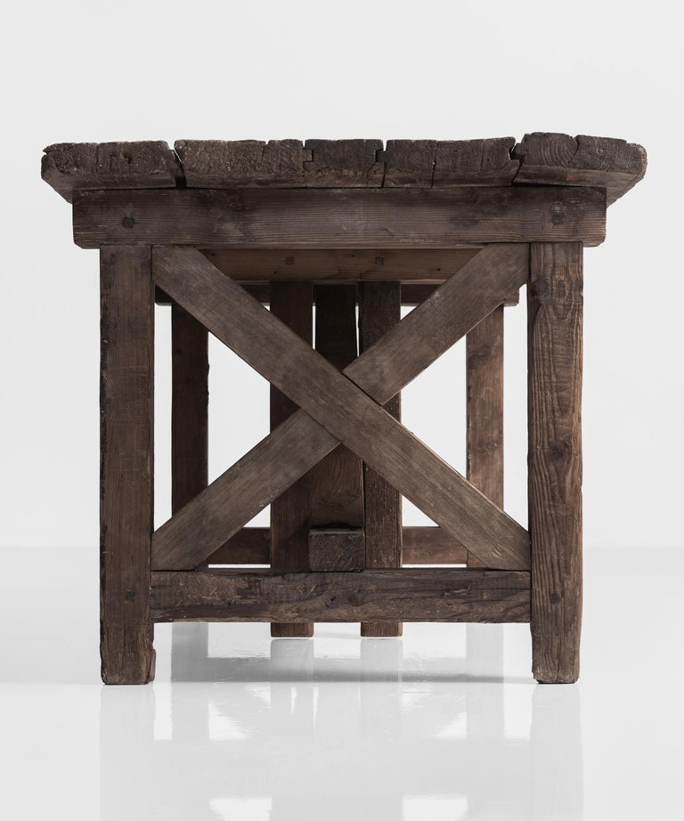 Primitive pottery table, France, circa 1880.  Solid construction with X-frame ends and 5-slatted top.