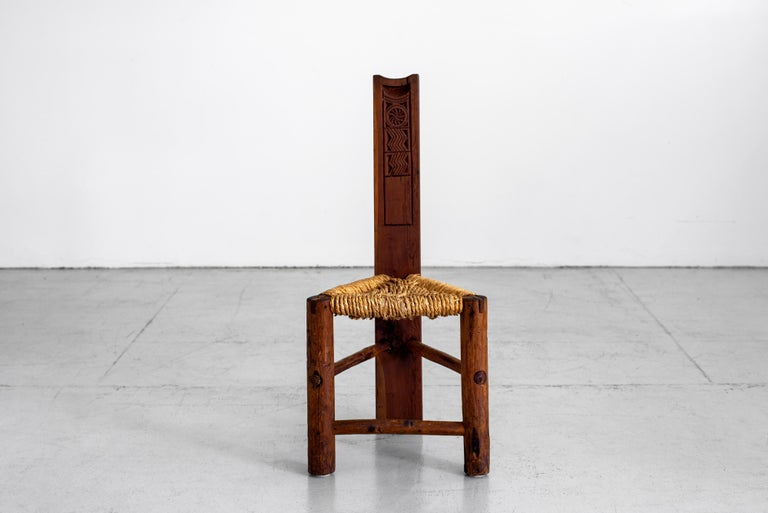 Primitive triangular wood chair with detailed carving and woven rush seat.