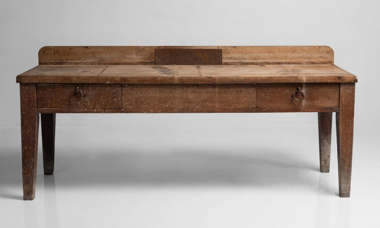 Primitive side board, France, 19th century.  Large rustic work table with oak plank construction and original iron hardware.