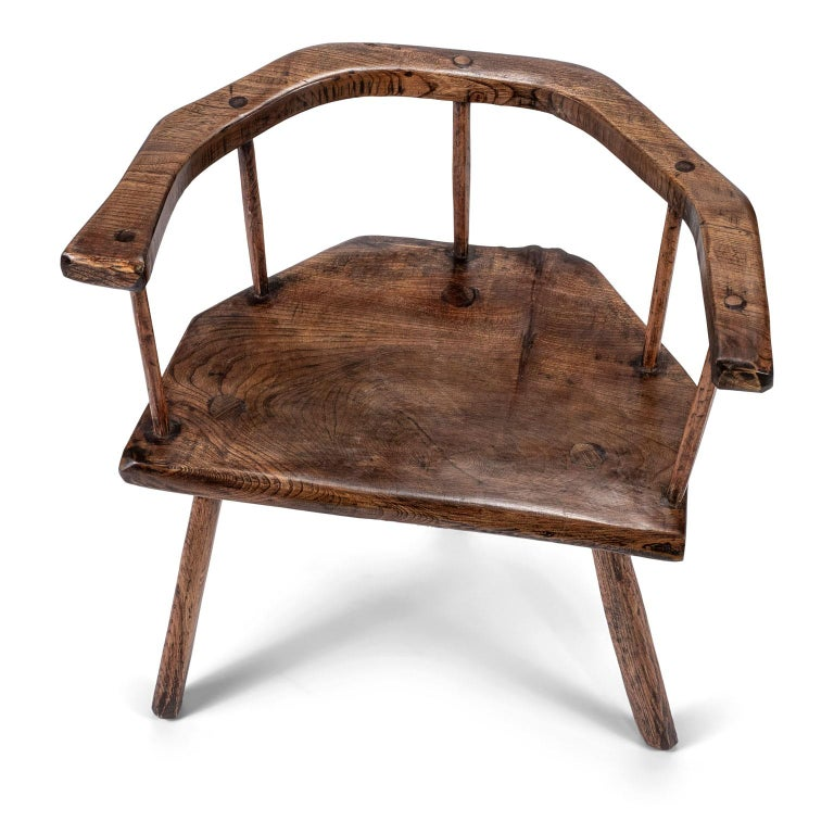 Primitive British stick chair hand-carved in elm and ashwoods. Carved elm horseshoe back rail and seat. Ash spindles and legs. Pegged construction. Gorgeous wood grain and patina. English in origin and dates to the 19th century.