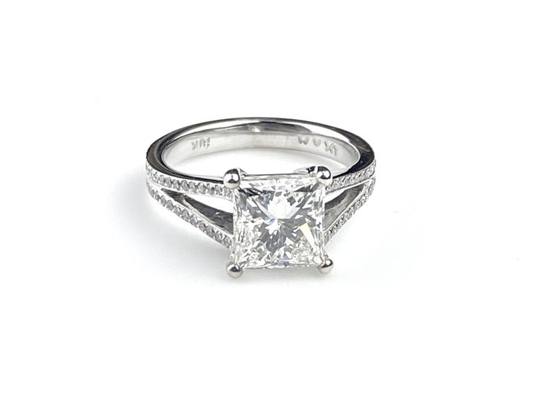 Split shank solitaire engagement ring set with 2.21ct Princess Cut center diamond, H VS1 GIA #2127143292. Setting in 18kt white gold with round cut side diamonds totaling 0.22ct. Side diamonds are F/G colour and VS/SI1 clarity. Current ring size 5.