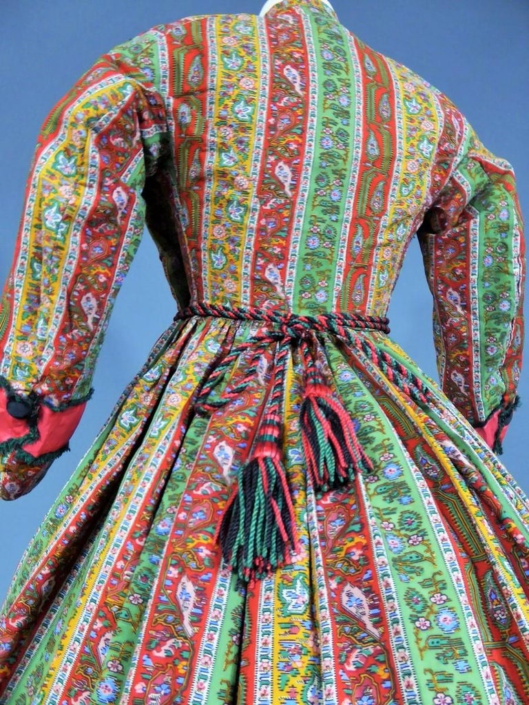Circa 1860  Europe  Beautiful dress with crinoline walk or indoor printed bunting bayadère dating from the French Second Empire. Fine print on roll or Alsatian from English wool (?) . Wide strips of cherry red satin -lined emerald frayed in the
