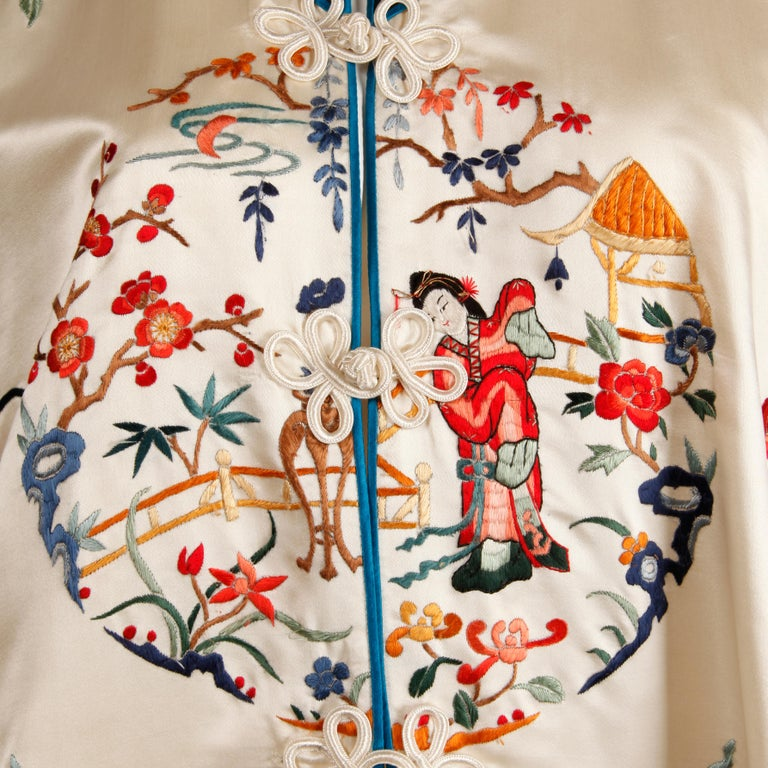 Stunning and pristine 20th C. Chinese silk satin robe with colorful embroidery of figures and cherry blossoms. Fully lined in silk with front frog button closure. The bust measures 44