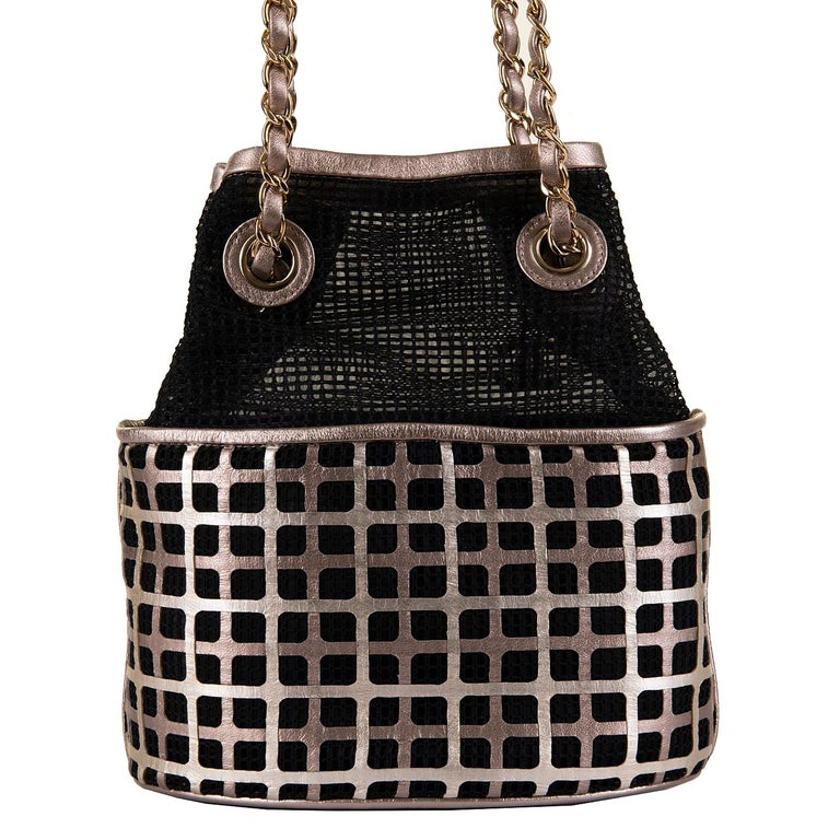 Never worn, this stunning Chanel Evening bag, is finished with a black mesh & metallic leather geometric design with goldtone hardware, accented with the iconic double 'C' chain pendant. The bag comes with it's original box, dust sack, packaging &