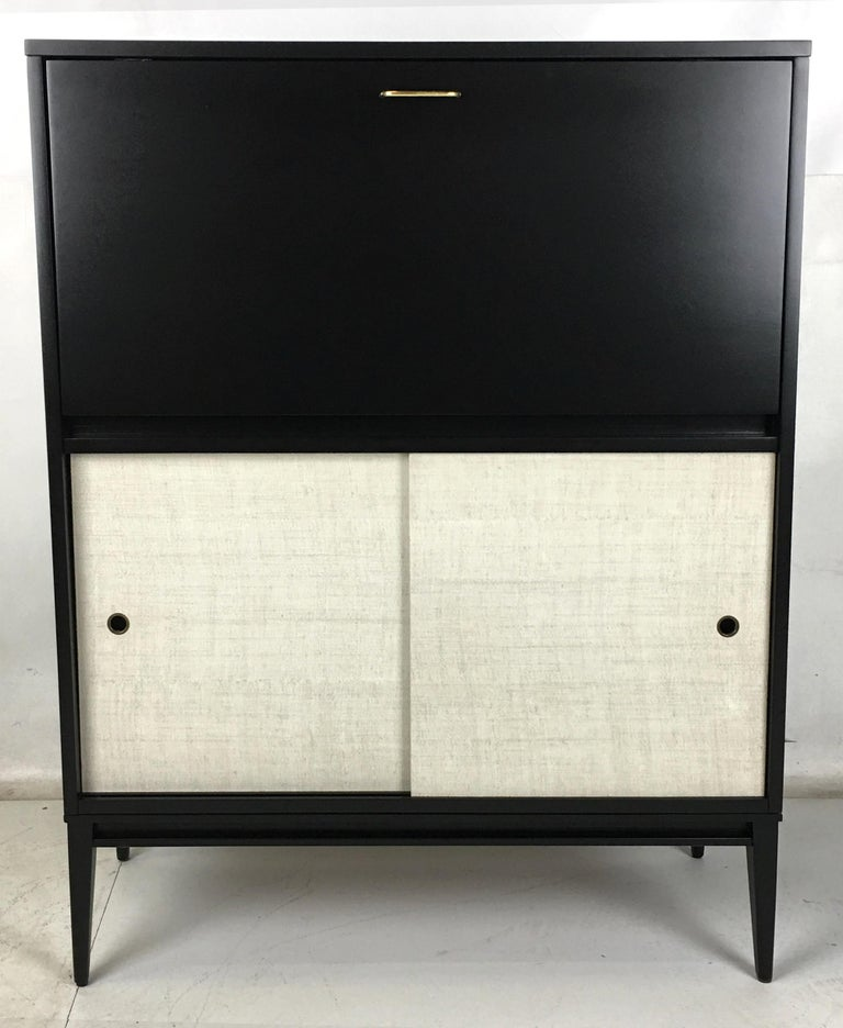 Up for bid is this handsome drop-front secretary from the Planner Group by Paul McCobb for Wichendon Furniture. The piece has been meticulously restored and refinished and couldn't be in nicer condition. The enameled Raffia doors are clean and