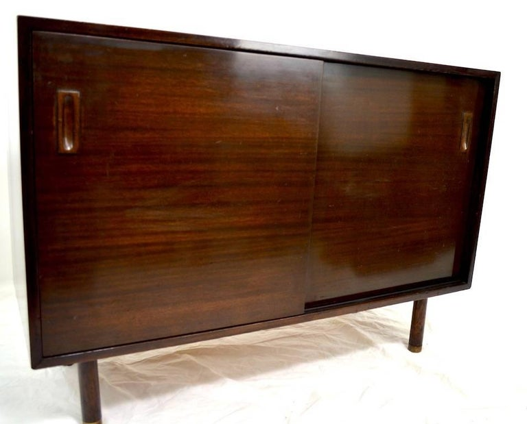 Dark mahogany two sliding door cabinet. One side opens to interior drawers, the other opens to an adjustable shelf. Good, original, unrestored condition, showing some cosmetic wear to finish, normal and consistent with age. The back legs are missing