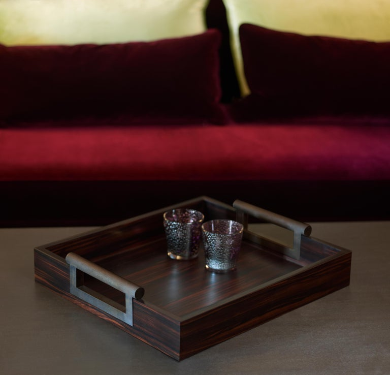 Alfred is a wooden tray with hammered bronze handles, with an essential but elegant style. .