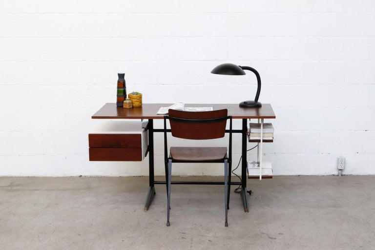 Charming modernist writing desk with floating teak top for Marko. Lightly refinished with teak floating side drawer and 2 tiered storage shelf on black enameled metal frame. In good overall condition with white metal accents. Some visible wear to