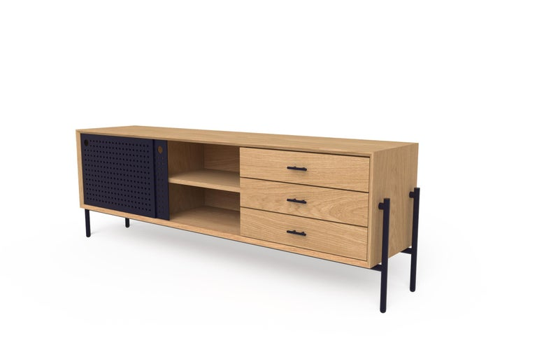 This simple and functional piece was originally conceived for TV rooms.  Its metal sliding doors have a pattern of perforations which allow for remotes to control interior devices. It's made of white oak wood and includes three drawers with metal