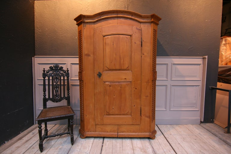 Provincial cabinet from the Empire period, circa 1820. Gusset cupboard or split cupboard made of solid pinewood. Standing on 4 pressed ball feet with bevelled corners with carved floral decoration. Curved cornice. One door made with 2 panels and