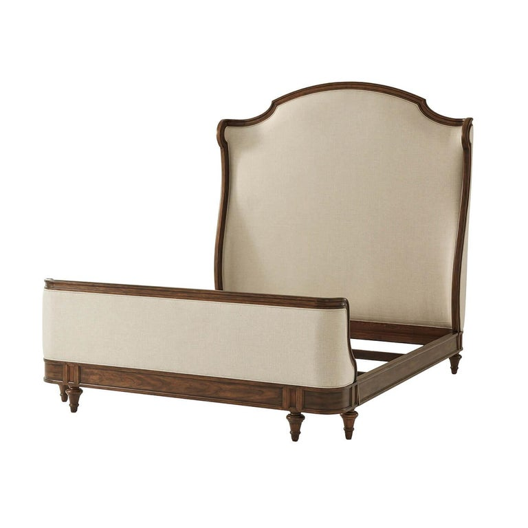 A French Provincial carved king size bed with an arched and molded upholstered headboard with scroll wings, an upholstered and hand carved framed low footboard and paneled rails on turned and tapered taupee feet. Dimensions: 65.75