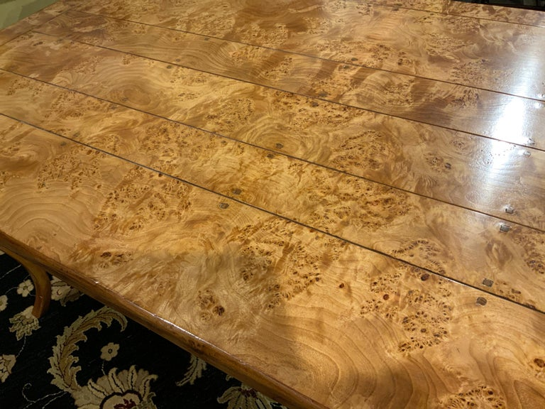 This rectangular burl elm wood top mounted to a conforming frame and raised On shaped cabriole legs.