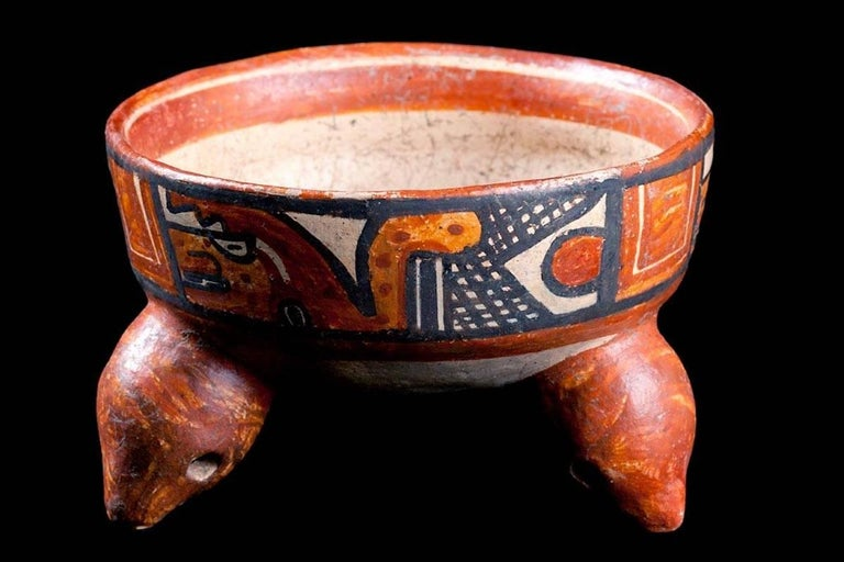 Papagayo polychrome pottery bowl, Mandador variety. Round bottomed bowl rests on three animal headed rattle legs. Exterior painted wide band with two stylized plumed serpents of jaguars with short snouts. Each panel is framed in black, separated by