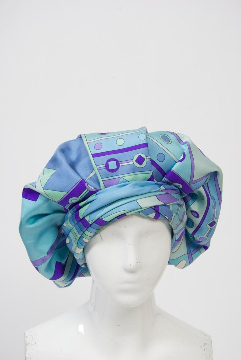 Custom-made hat crafted of Pucci blue/purple silk print in an expanded beret style featuring a pleated turban-style band that circles the head. Emme was a high-end New York millinery, known especially for its custom hats. From 1952-62, Adolfo was