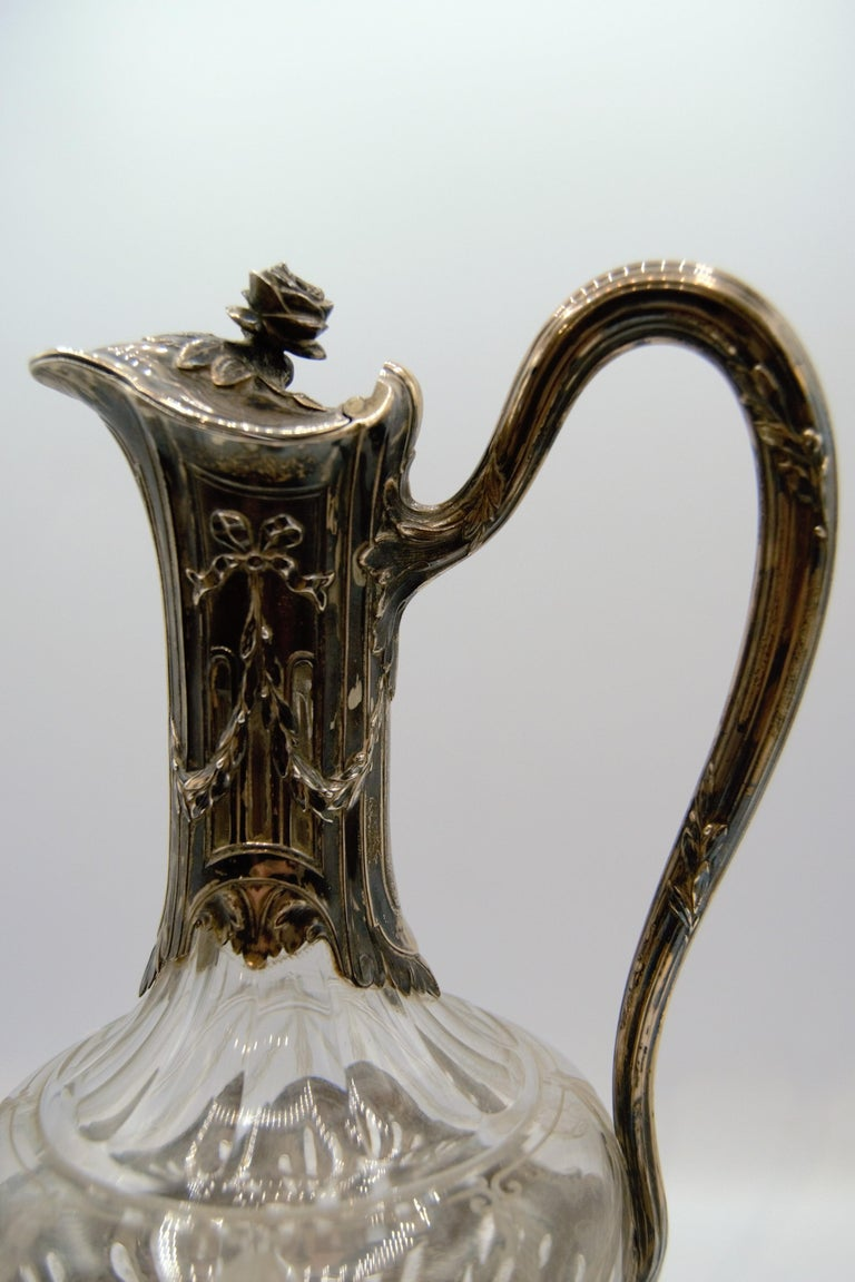 Ewer or wine carafe in glass engraved with garlands and drops, with collar frame, handle and pedestal in silver decorated in suits with knotted garlands. Minerva and silversmith hallmark. Measure: Height: 11.23 in  Aiguière ou carafe à vin en verre