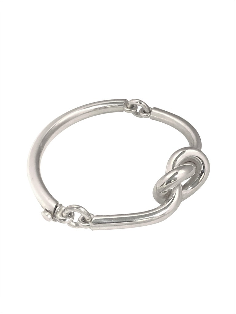 Circa 1980 Puig Doria Sterling Silver Bracelet, comprised of Curved Solid links with a central nautical style knot. The top of the bracelet Knot section measures 1 X 3/4 inch with the bar sections being 3/16 inch thick. Inside, Wrist measurement 6