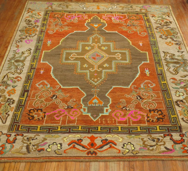 Pumpkin Orange color 20th century Turkish Kars square size rug with a large graphic brown medallion surrounding 4 people and a large scale gray floral border. Is it Masculine or Feminine? You can say its both. Measures 10'9'' x 12'9'' dated 1931.