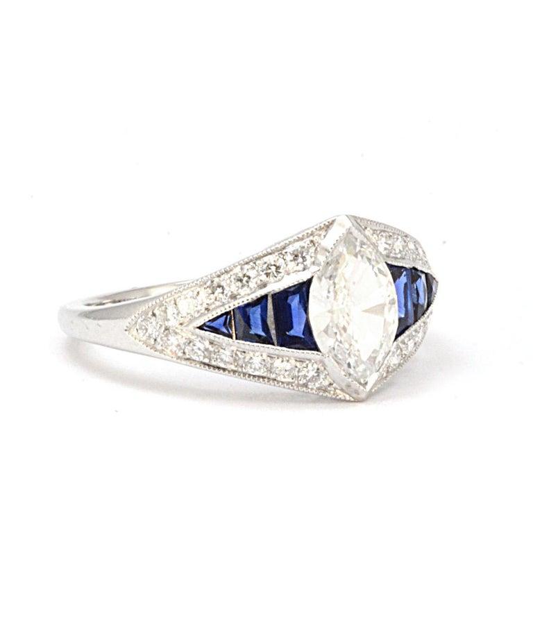 Pure Platinum Natural Marquise Diamond & Genuine Sapphire Ring! Size 6.5! This diamond ring has a center marquise diamond, and 13 diamonds down the sides approximately .105CTTW and 6 genuine sapphires. The marquise measures approximately 0.90ct, and