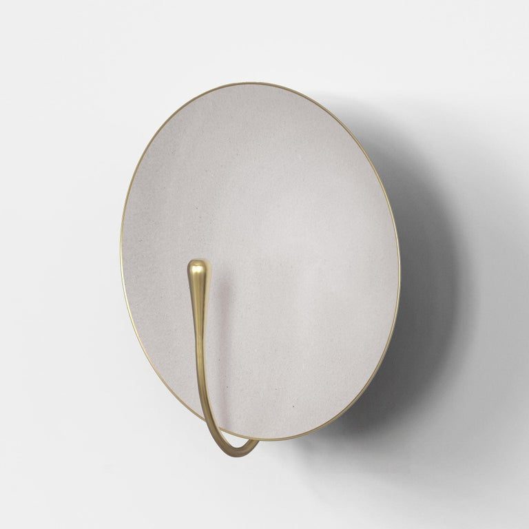 A gentle silhouette of a plate makes up this unique wall light. The back and edges of the lamp are finely kept in original brass whilst the inside of the plate is finely lacquer in a matt white finish.  This light fixture combines comfortably with