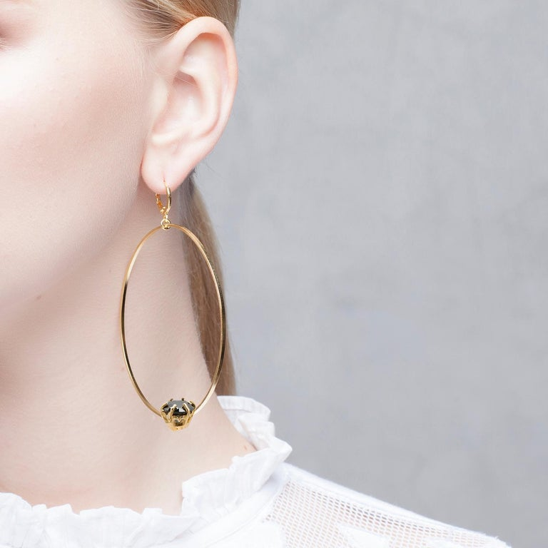 Puro Iosselliani presents its iconic creole big hoop earrings. Made in 18 Karat gold plated silver, the big hoops float effortlessly by a lever back vintage hook. A reversed black round zircon embellishes the hoop for extra shimmering. 6,5 cm
