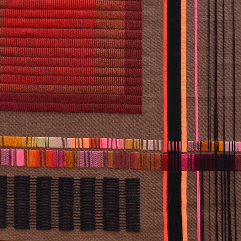 Vibrant abstract geometric textile artwork by Delphine A. Davidson (signed), Edinburgh, circa 1970-1980. The composition of horizontal and vertical lines is embroidered in bright colored wool on a brown loosely woven fabric that is stretched over a