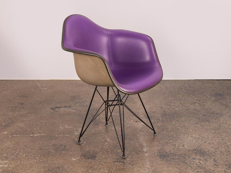 1960s Padded Eames Armshell Chair on the black eiffel base. In a stylish, rare purple color! The padded vinyl is in good condition, very clean with only a small closed tear on the bottom right. Add a classic touch of midcentury to any room with this