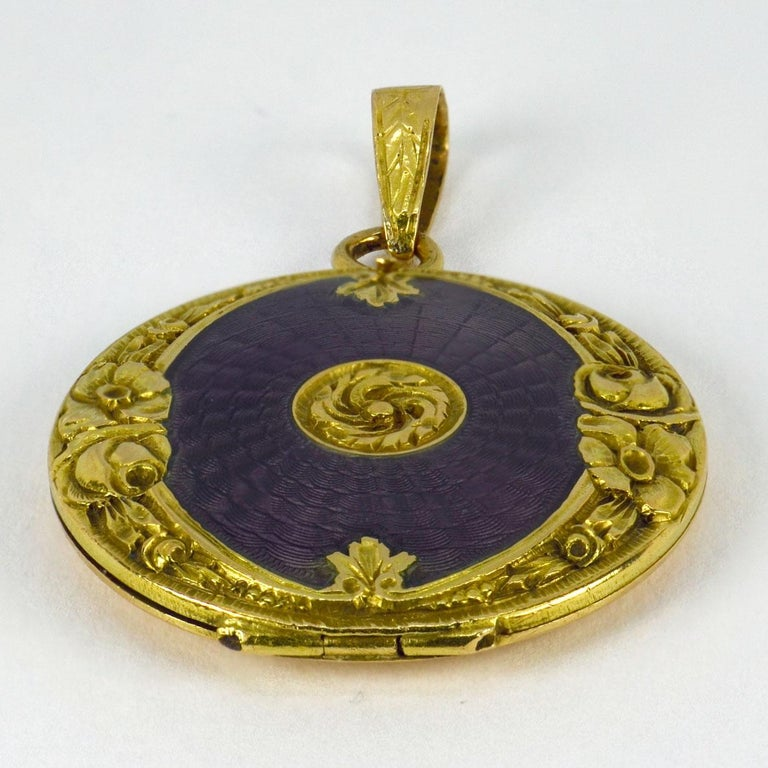 An 18 karat (18K) yellow gold pendant locket with purple guilloche enamel and a floral frame. Scratch numbered 028. Unmarked but tested as 18 karat gold.  Dimensions: 2.8 x 2.4 x 0.35 cm (not including jump ring) Weight: 5.99  grams